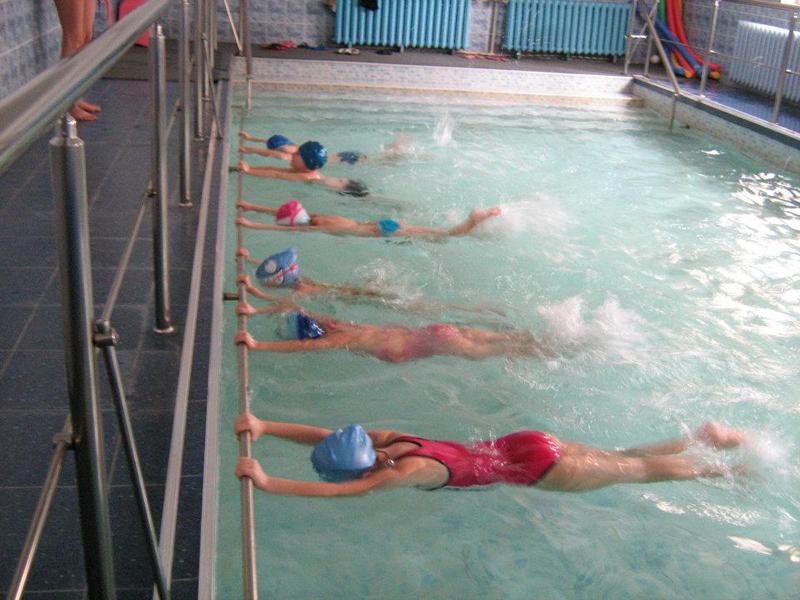 Деца в басейн се учат да плуват