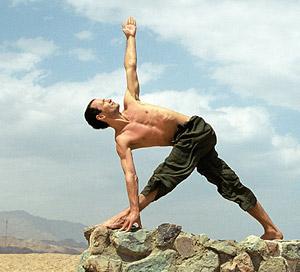 Мъж прави йога упражнения на открито